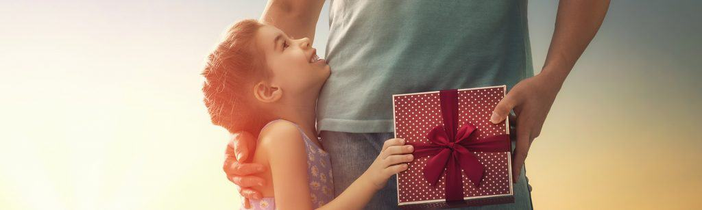 Young girl hugs dad from side while handing him a Father's Day gift