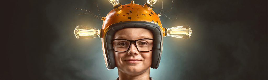 Young child inventor faces camera with goggles and a helmet on, lit light bulbs coming out of the helmet