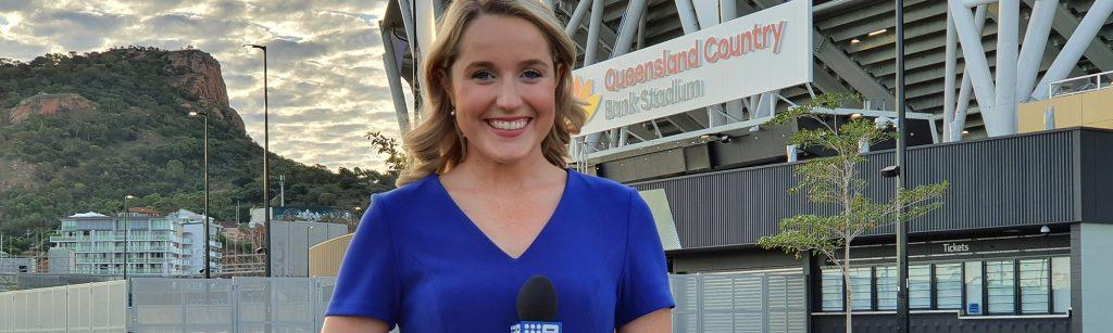 Erin Buchan stand in front of sports stadium with blue dress on and reporting microphone in her hands, ready to go