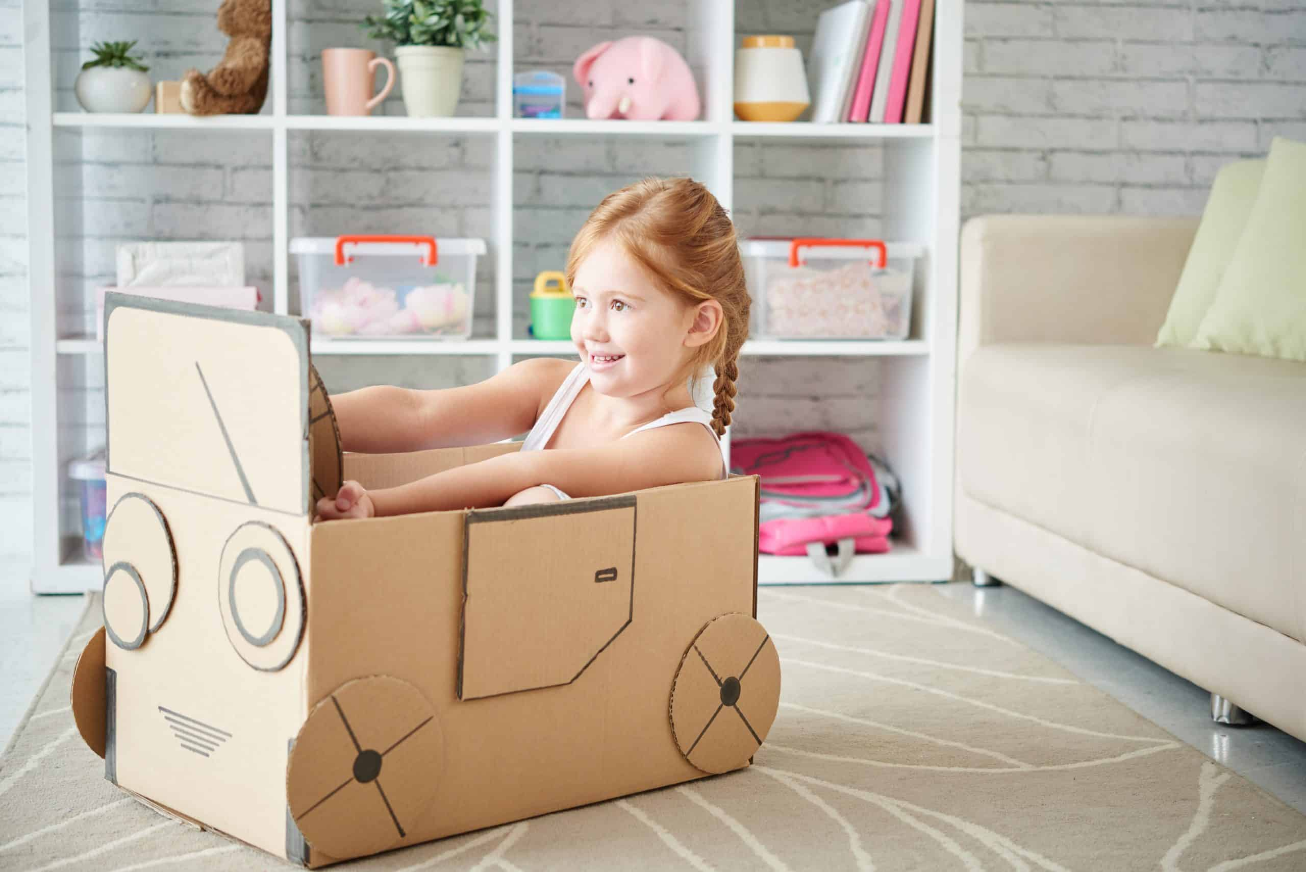 Young girl sits in the cardboard box car she made at home, pretending to drive and smiling