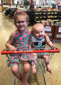 Two young children sit in trolley inside supermarket with wide smiles (Cliffo's Chidlren)
