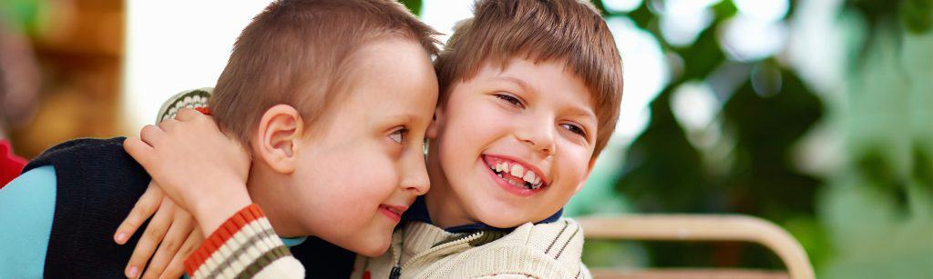 Two young boys with disabilities hug and smile widely