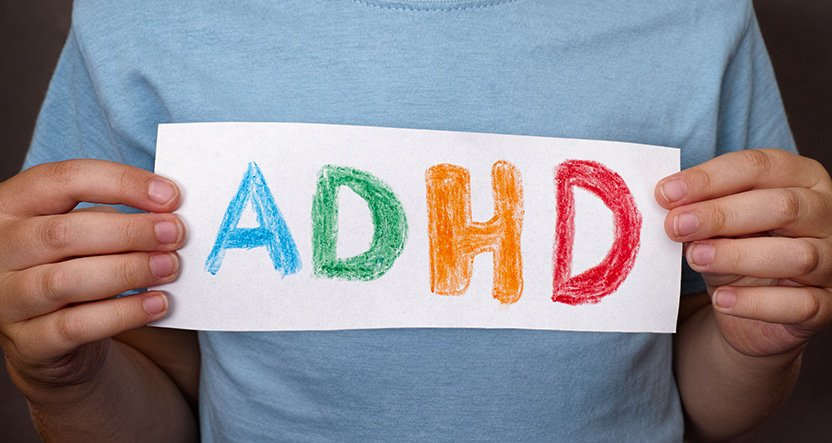 close up of child holding piece of paper that has coloured letters 'ADHD'
