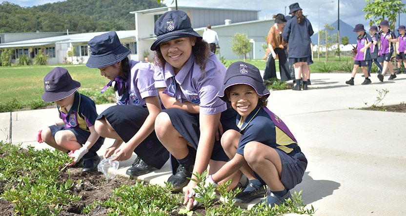 Children MacKillop uniform bend down next to grass