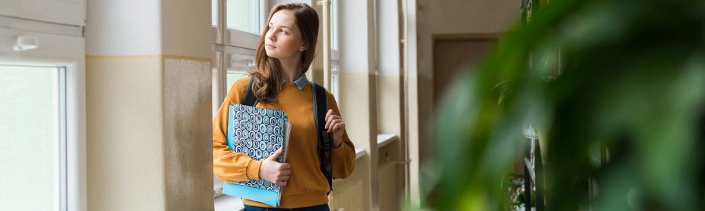 Young girl in high school corridor leans on window and looks outside, sdchool bag slung over shoulder and holding book
