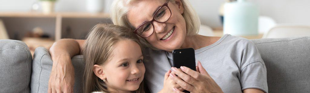 21st Century Grandmother and young girl sit on couch and look at phone together, smiling