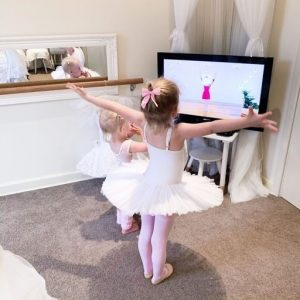 Two young girls in leotards follow Ballet Lessons at Home on TV through Ballet Time