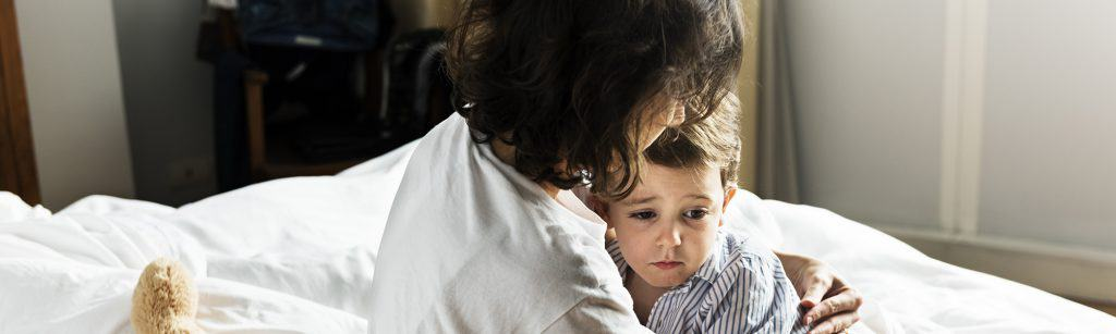 Mother holds young, scared son in her arms at home to comfort him