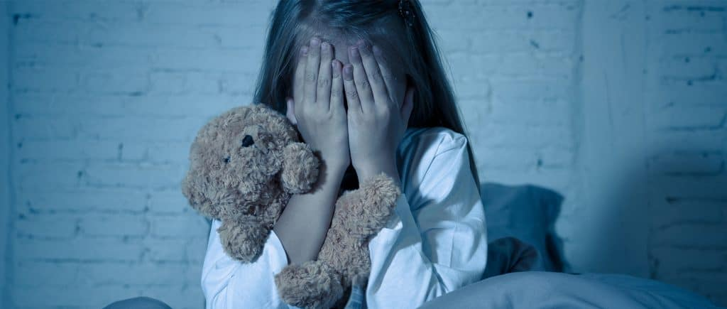 Young girl in dark room covers eyes with hands while clutching teddy bear