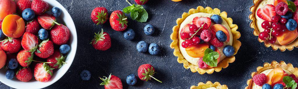 Birds eye view of sweet summer tarts covered in berries, next to big bowl of berries and fruit