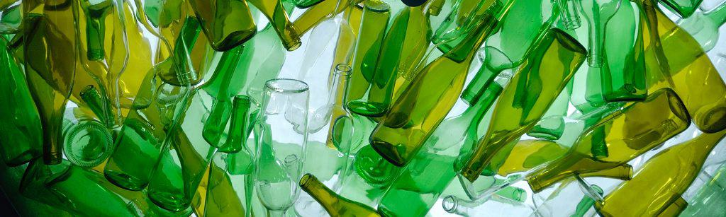 Different coloured green and clear glass bottles all lying on each other, ready for recycling