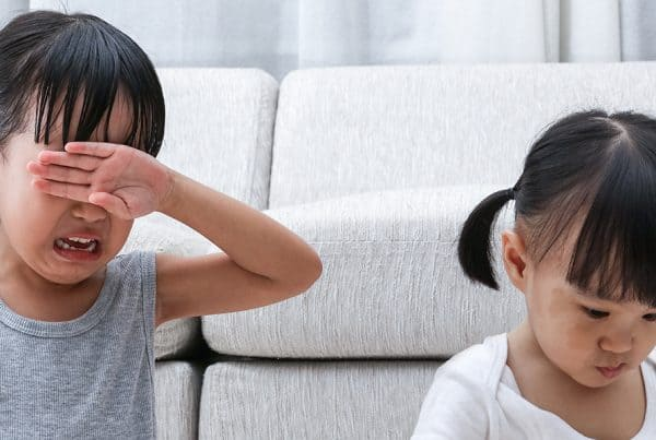 Two young girls at home have sibling rivalry, sit in front of couch, one playing with toys while the other cries and is upset