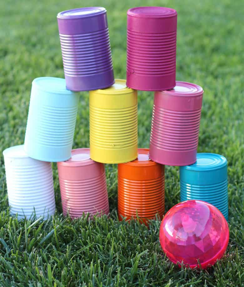 Painted tin cans stacked on eachother on grass outside, next to small pink ball