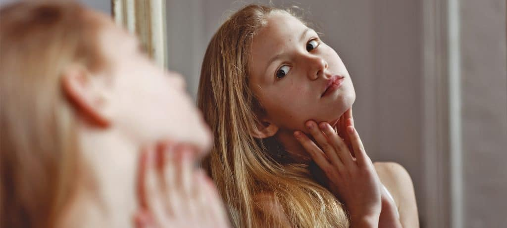 Teen girls checks acne, a common skin issue that teenagers (and older people) deal with