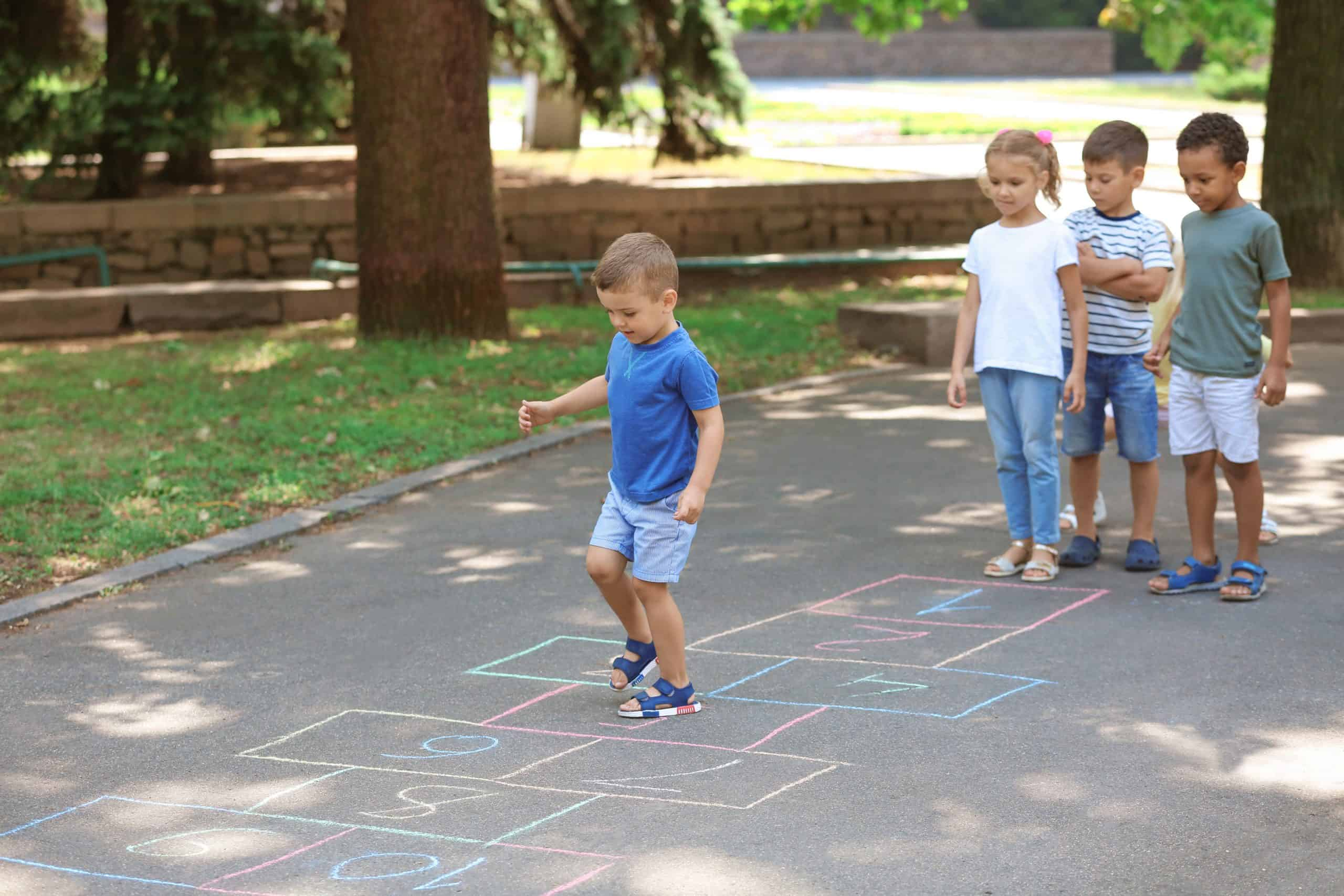 children play an old school game of hopscotch
