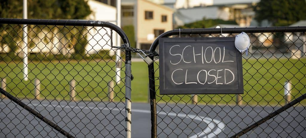 school gates closed with 'school closed sign' and mask due to crazy year of 2020 and coronavirus