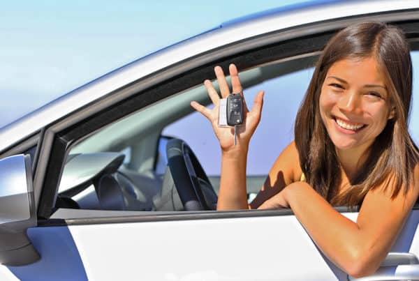 Teen holds keys happily after receiving license