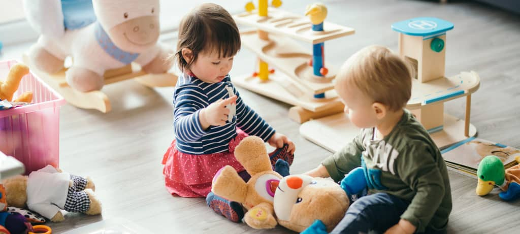 Two toddlers play with safe toys