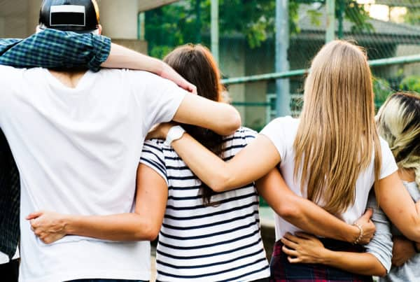 teen friends wrap arms around each other