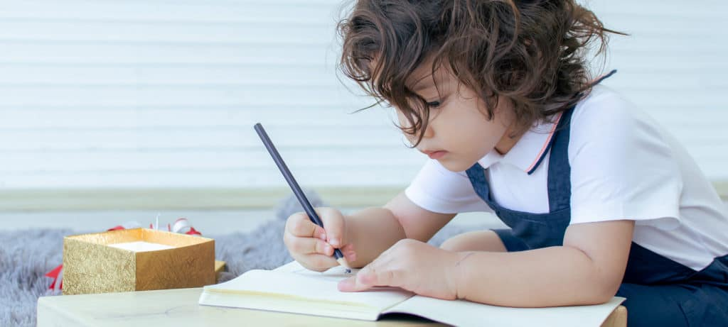 Child draws on paper