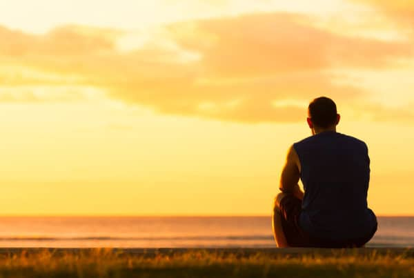 Man experiencing grief looks off to sunset
