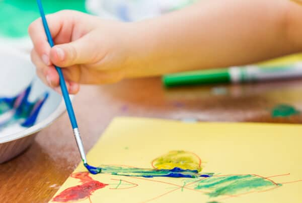 young girl doing arts and craft with paint and more