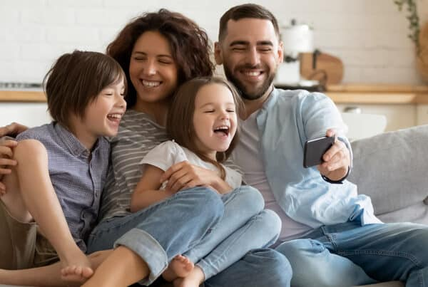 family sitting on couch together laughing