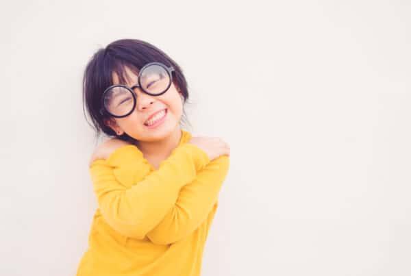 young girl smiles and hugs herself